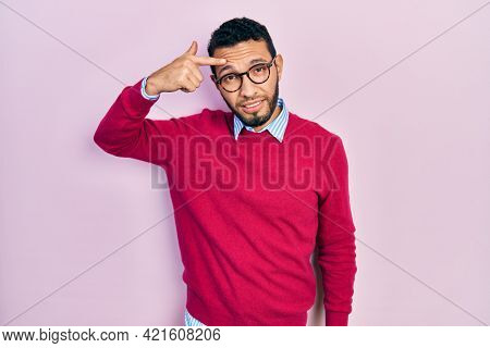 Hispanic man with beard wearing business shirt and glasses pointing unhappy to pimple on forehead, ugly infection of blackhead. acne and skin problem