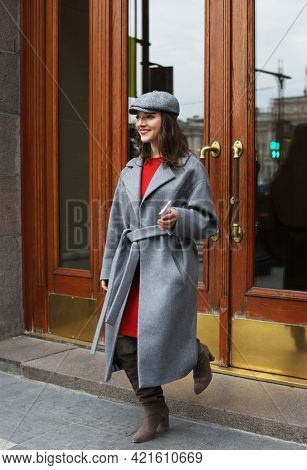 Lifestyle and people concept: Outdoor portrait of yong beautiful happy smiling woman wearing stylish grey hat, coat. Young female leaving the hotel for a walk . Autumn day.