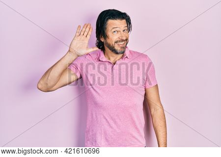 Middle age caucasian man wearing casual white t shirt waiving saying hello happy and smiling, friendly welcome gesture