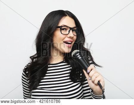 Young brunette woman in striped shirt and glasses holds microphone and prepares to sing in karaoke over grey background