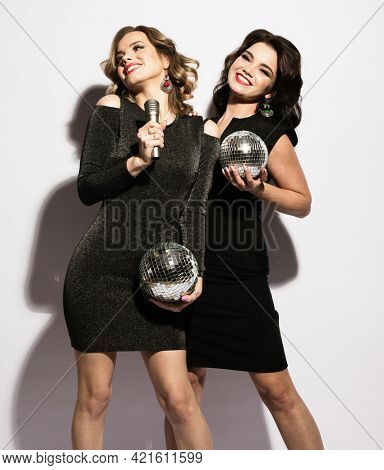 Two charming ladies dressed in black cocktail dresses sing songs from a microphone, hold disco balls