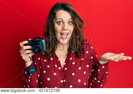 Young caucasian woman holding reflex camera celebrating achievement with happy smile and winner expression with raised hand