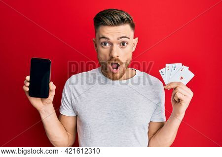 Young redhead man holding smartphone and casino card afraid and shocked with surprise and amazed expression, fear and excited face.