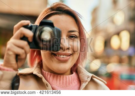 Young hispanic girl smiling happy using reflex camera at the city.