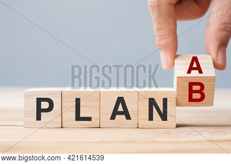 Businessman Hand Flipping Wooden Cube Blocks With Plan A Change To Plan B Text On Table Background.