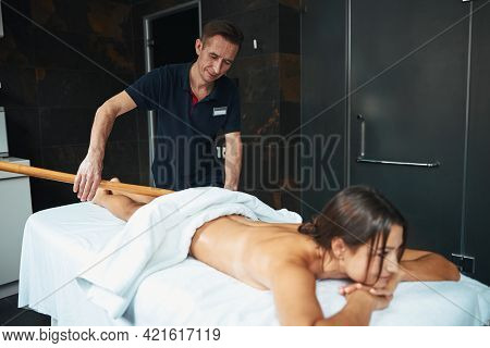 Adult Caucasian Massage Therapist With Special Tool Making Anti Cellulite Massage In Wellness Center