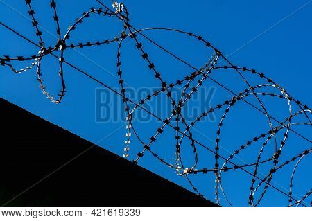 Barbed Wire Against The Sky. Restricted Area Fence With Barbed Wire