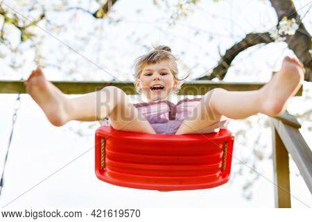 Happy Little Toddler Girl Having Fun On Swing In Domestic Garden. Smiling Positive Healthy Child Swi
