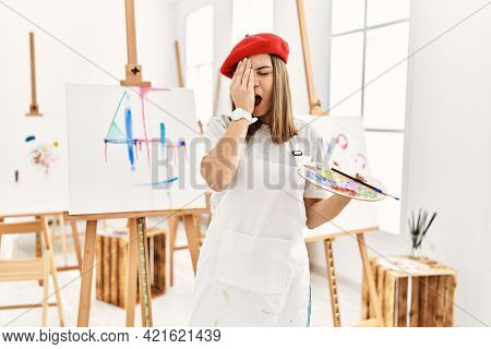 Young artist woman painting on a canvas at art studio yawning tired covering half face, eye and mouth with hand. face hurts in pain.
