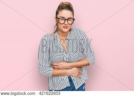 Young caucasian woman wearing business shirt and glasses with hand on stomach because indigestion, painful illness feeling unwell. ache concept.