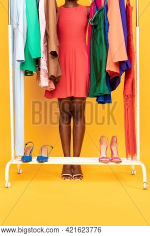 Unrecognizable Shopaholic Lady Choosing Outfit Shopping On Yellow Bacground, Cropped