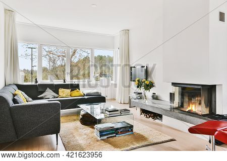 White Light Living Room With L Shaped Couch With Colorful Cushions And Fireplace With Granite Shelf