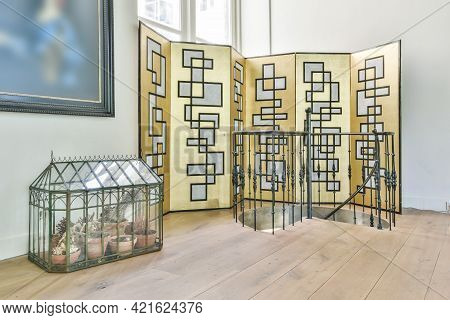Spacious House Hallway With Shiny Golden Folding Screen At Spiral Staircase And Small Glass Box Cons