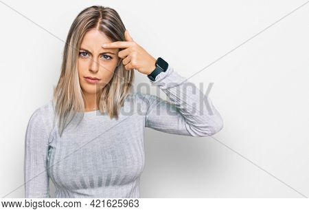 Beautiful blonde woman wearing casual clothes pointing unhappy to pimple on forehead, ugly infection of blackhead. acne and skin problem