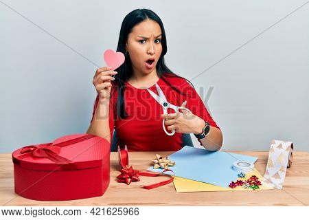 Beautiful hispanic woman with nose piercing doing handcraft heart in shock face, looking skeptical and sarcastic, surprised with open mouth