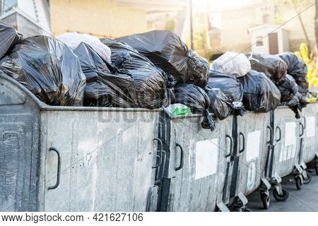 Rows Of Many Big Metal Overloaded Dumpster Cans Full Of Black Plastic Trash Litter Bags Near Residen