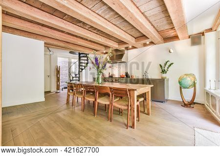 Cozy Light Room With Wooden Floor And Beamed Ceiling Above Wooden Dining Table And Chairs In Dayligh