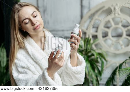 Smiling Woman In Soft Bathrobe Choosing Bottles With Cosmetics For Skin Care. Female In Bathrobe Sta