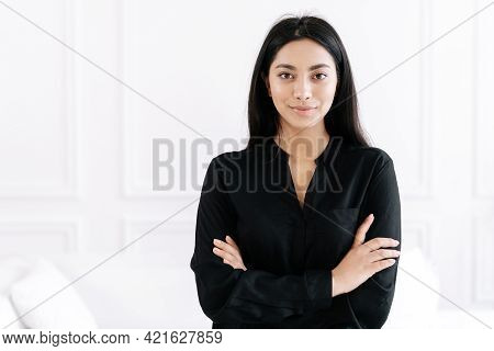 Portrait Of Confident Young Beautiful Asian Businesswoman With Crossed Arms Smiling And Looking Frie