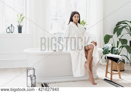 Attractive Young Asian Woman Sitting In Light Spacious Bathroom With Green Plants Wearing White Bath