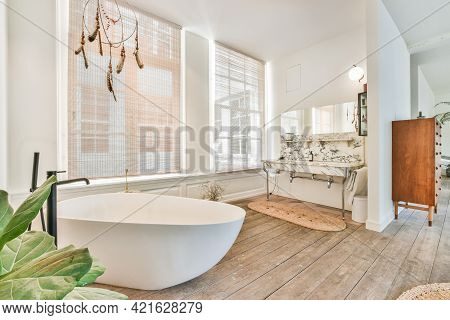 Spacious Open Bathroom Area With Soaking Tub And Double Marble Sink Under Mirror Near Big Windows In