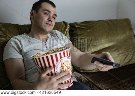 A Man At Home Sitting On The Couch With A Large Bucket Of Popcorn Switches Tv Channels Using The Rem