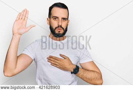 Young man with beard wearing casual white t shirt swearing with hand on chest and open palm, making a loyalty promise oath