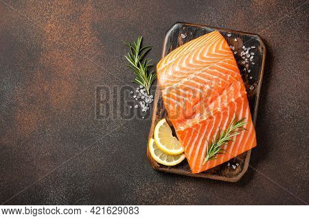 Fresh Salmon Fillet On Wooden Board And Spices For Cooking