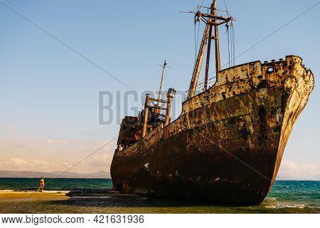 Travel. Tourist Woman On Beach Near The Famous Rusty Shipwreck In Glyfada Beach Near Gytheio, Gythio