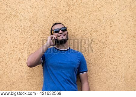 Young Latino Man With Sunglasses In A Phone Call. Standing At A Yellow Wall. Technology Concept
