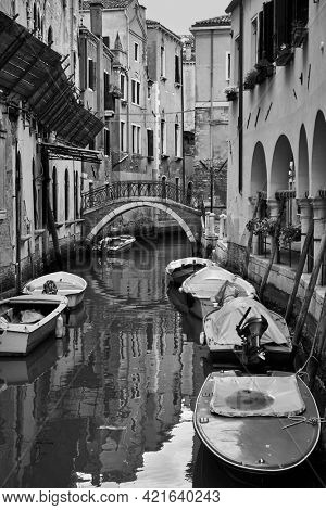 Canal in Venice with moored boats, Italy. Black and white photography, venetian view