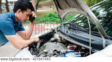 Angry Asian Man And Using Mobile Phone Calling For Assistance After A Car Breakdown On Street. Conce