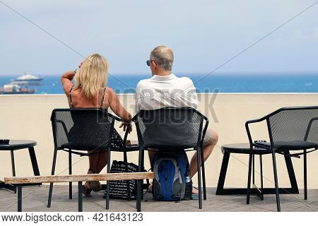 Monte-carlo, Monaco - June 16, 2019: Rear View Of A Couple Of Tourists Sitting At A Bar And Looking