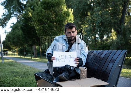 Young Sick Helpless Desperate Homeless Man Sitting On The Bench On The Urban Street In The City Hold