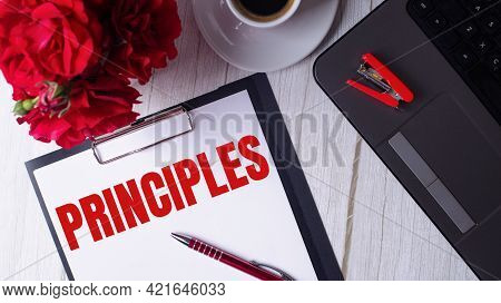 The Word Principles Is Written In Red On A White Notepad Near A Laptop, Coffee, Red Roses And A Pen.