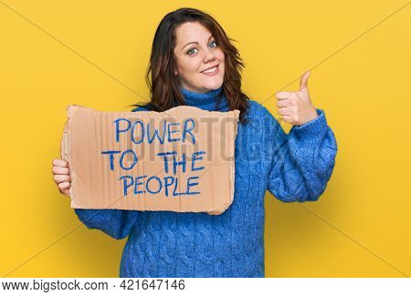 Young plus size woman holding power to the people banner smiling happy and positive, thumb up doing excellent and approval sign
