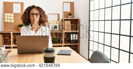 Middle age hispanic woman working at the office wearing glasses asking to be quiet with finger on lips. silence and secret concept.