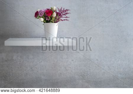 Spring Flowers On Floating White Shelf Against Concrete Wall Design