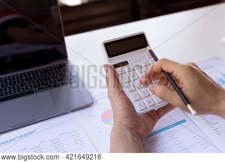 Hand Holding Pencil And Press Button Calculator. Financial And Tax Systems Concept.