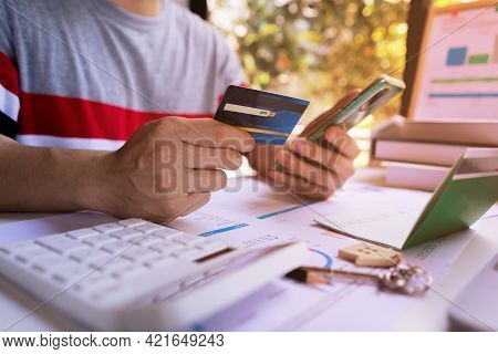 Young Man Holding Credit Card And Using Mobile Smartphone To Online Shopping, E-commerce, Internet B