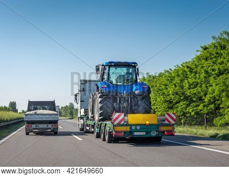New Blue Tractor On Long Trailer Platform Of Truck For Transporting Heavy Machinery On Highway. Tran