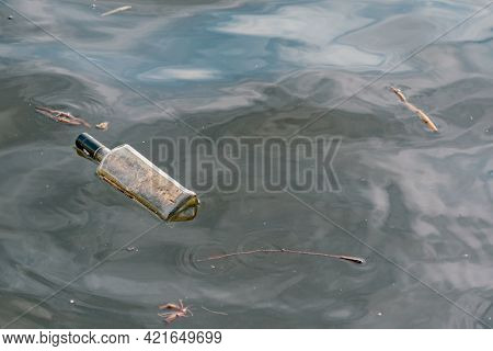 Dirty Glass Empty Bottle Floating In Water. Pollution. Dangerous. Nature. Human Impact. Rubbish. Haz