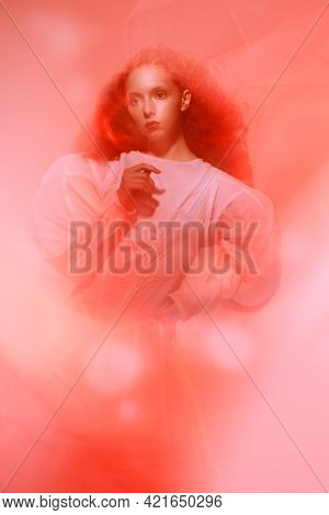 Portrait of a refined female model with lush red curly hair posing in a long white art dress in red haze. Art fashion. Studio shot.