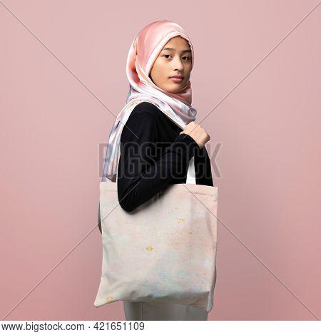 Muslim woman carrying a tote bag