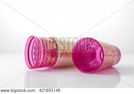 Traditional moroccan empty tea glasses or tumblers on white background. Decorative, ornamental Middle Eastern glassware product.