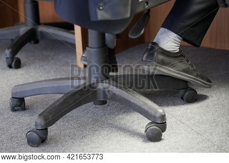 The Legs Of An Office Clerk Or Dispatcher On Duty Sitting On A Pneumatic Chair With Wheels. Concept