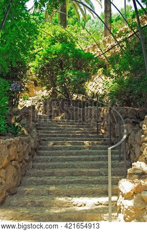 Stairs To The Archway. Path Covered With Plants In The Gardens Of Guell Park. Architecture Details B