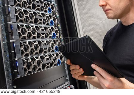 Male It Support Professional With Digital Tablet Examining Hyper Converged Server Hardware