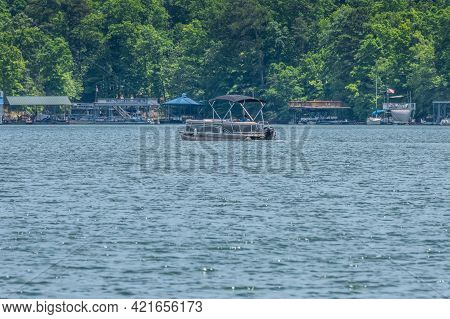 A Man Driving A Pontoon Boat With A Canopy Cruising Slowly Along The Floating Boat Docks At The Shor