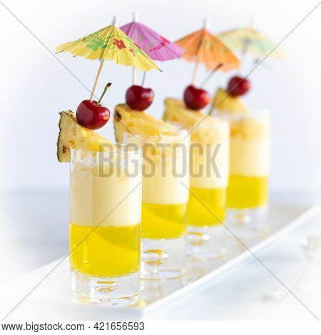 Close Up Of A Row Of Pineapple Jelly Parfaits Against A Bright Background.